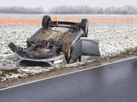 Overturned Car Beside the Wet Road on a Winter Day Stockfoto