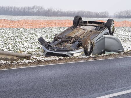 Overturned Car Beside the Wet Road on a Winter Day