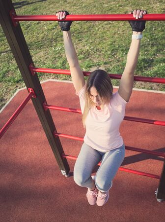 Young Athletic Woman Exercising on Wall Bars in the Park