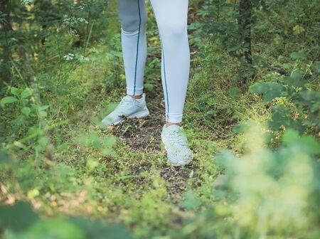 Female Runner in Sportswear Standing in Dense Forest Closeup on Legs