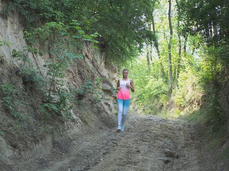 Young Blonde Caucasian Female Running in Forest on a Dirt Road