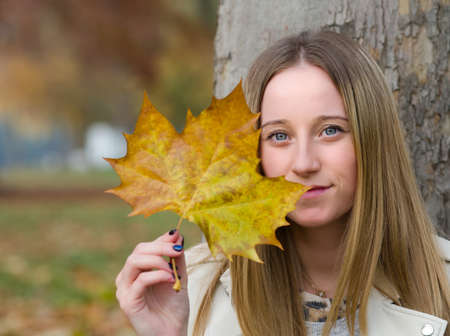 Portrait of a Young Beautiful Blonde Woman in Autumn Park with Maple Leaf