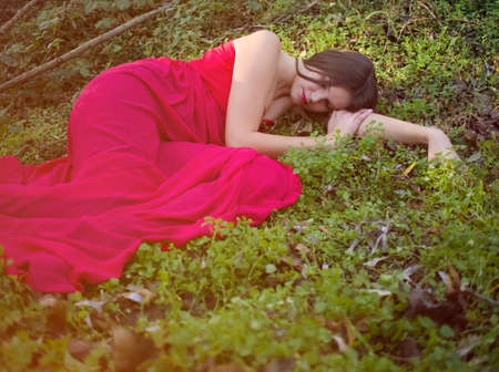 Young Beautiful Long Haired Brunette Woman in Red Dress Sleeping in the Forest