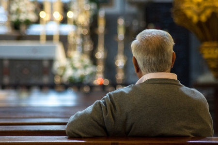 grizzled: An older man in church thinking.