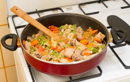 stew pan: Pork stew cooked in a frying pan. Wooden spoon