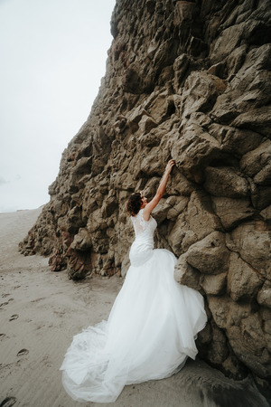 The bride wants to escape climbing a cliff on the beach. Is joking.