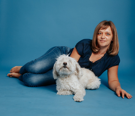 Woman girl sitting on the floor with a white dog. On a blue background.