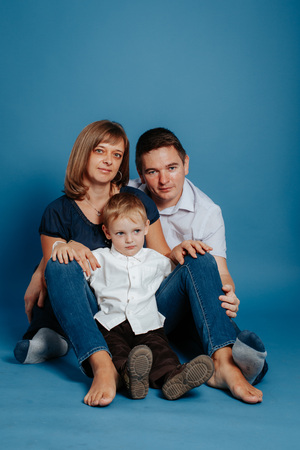Family mom dad and baby are sitting on the floor. On a blue background. 写真素材