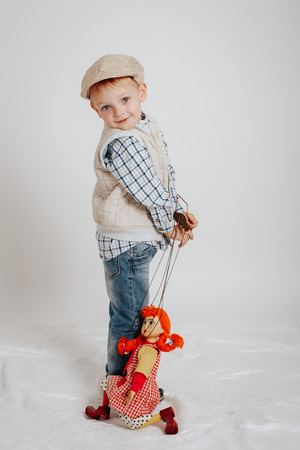 A little boy is standing and playing with a puppet doll. Standard-Bild