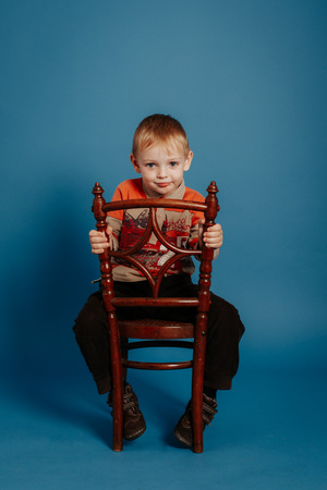 A little boy in a cap sits on a chair and smiles. On a blue background