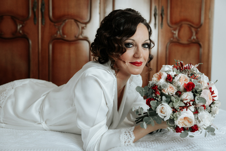Bride with a bouquet of wedding flowers lying on the bed. Attractive young bride lies next to the dress and winter bouquet. Morning bride in a luxury hotel