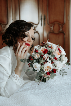 Bride with a bouquet of wedding flowers lying on the bed Reklamní fotografie