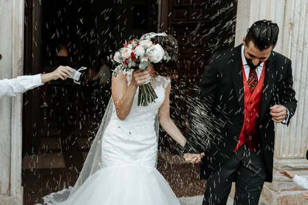 People throw rice on newlyweds walking out of the church. Beautiful wedding tradition.