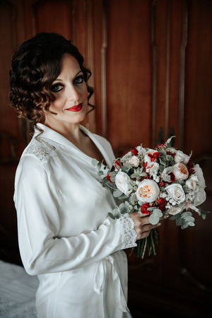Morning of the nice sexy bride with beautiful wedding bouquet on the bed Stock fotó