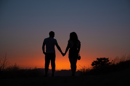 Young couple enjoying sunset in the mountains an amorous couple at sundown.