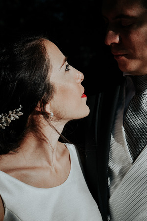 Close-up portrait young beautiful stylish wedding couple. Newlyweds hug and look at each other.