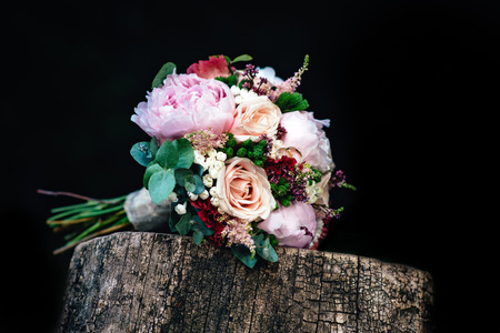 Wedding bouquet of roses with rings on wooden bench. Bridal bouquet of roses with rings.