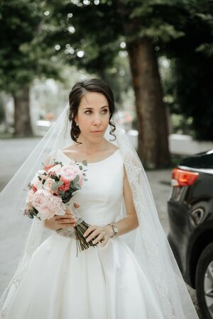 Beauty Portrait of bride wearing in wedding dress with voluminous skirt. Young attractive bride with bouquet of flowers. Smiling beautiful young bride Archivio Fotografico - 132210181