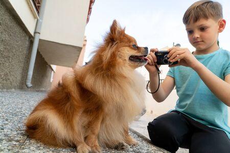 Adorable little boy shooting photos of his pomeranian dog with digital camera Imagens
