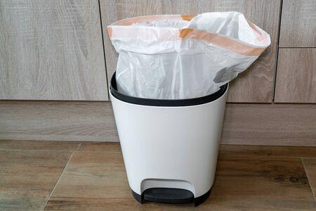 Garbage bin in the kitchen. Trash bin with plastic bag