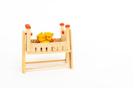 Toy wooden bed. Wooden toy bed with a cute pair of teddy bears on white background. Toy teddy bears sit toy beds. Cute wooden decor Stock fotó