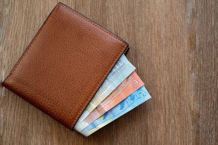 New leather wallet with euro money on a wooden background