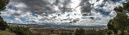 Wide angle landscape view of the city of Granada in Spain. The sky in black clouds