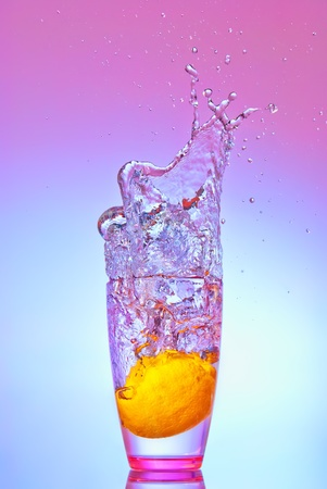 A lemon dropped into water or some alcoholic drink creating a splash. photo