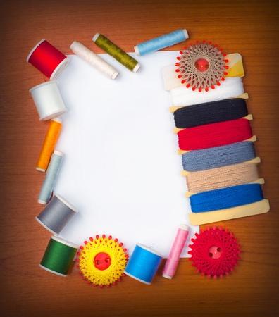 hilo rojo: Tarjeta blanca en la mesa con hilos de coser alrededor de la tarjeta.