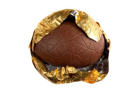 A chocolate Easter egg in the process of being unwrapped from the foil packaging. Stock Photo - 6831584