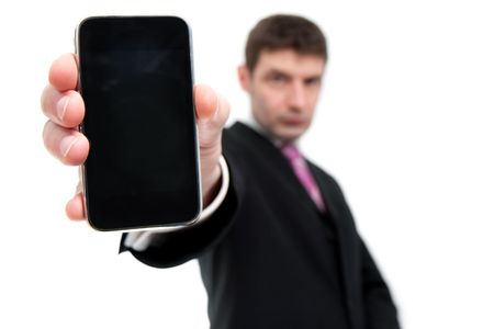 A mid thirties businessman in a black suit holds a smart phone in his hand close to the camera.  Differential focus on the phone photo