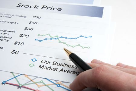 stock price: A male hand holding a pen reviews a page of a report containing the stock price of the company.