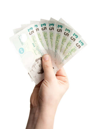 money pounds: A hand holding a number of �5 notes in a fan arrangement.