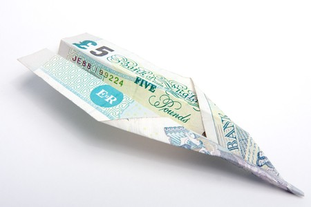 pound sterling: A paper plane made from a slightly battered British five pound note.  Studio isolated on a white background.