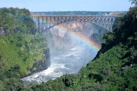 zambia: The Victorian bridge spans the Second Gorge at Victorial Falls.  A rainbow is formed from the waterfall spray.