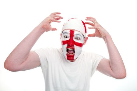 An English sports fan holds his hands in the air and looks shocked.  The fan has an England flag bandana and his face painted with the England flag.    Studio isolated on white. photo