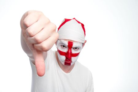 An English sports fan holds his hand out and does a thumbs down sign.  Differential focus on the hand.  The fan has an England flag bandana and his face painted with the England flag.    Studio isolated on white. Stock Photo - 7111382
