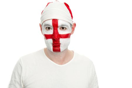 An English sports fan looks directly towards the camera.  The fan has an England flag bandana and his face painted with the England flag.    Studio isolated on white. Stock Photo - 7111398