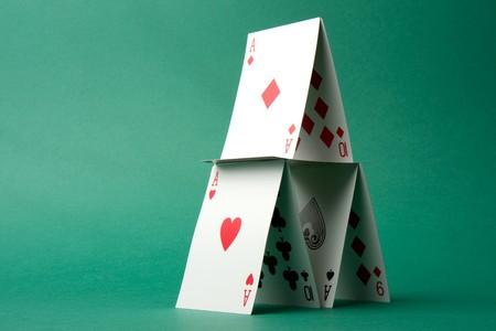 Ein Kartenhaus auf grünem Hintergrund.
