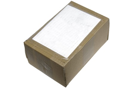 A brown cardboard box covered in tape and an address label.  The box is battered and the label is a bit dirty from going through the postage system Stok Fotoğraf