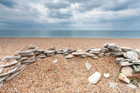 beach shingle: I resti di un muro di pietra su una spiaggia di ciottoli vuota nel Dorset, UK (Chesil Beach) Archivio Fotografico