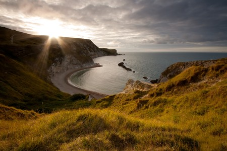 dorset: The sun peeps out over the cliff top over looking Man-O-War Cove on the Jurassic Coast in Dorset, UK.