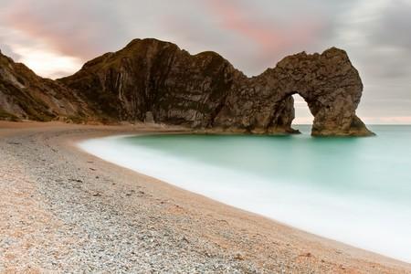 dorset: A 30 second exposure of the sunrise at Durdle Door on the Jurassic Coast in Dorset, UK.