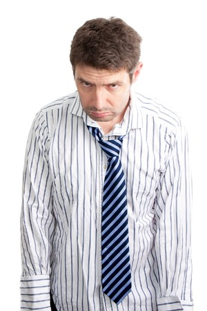 A grumpy looking businessman that looks like he has been up all night. His stripy blue tie is droopy, his shirt is creased and he has day old stubble. One person studio isolated on a white background. Stock Photo