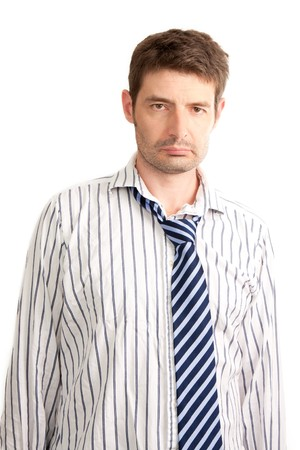 untidy: A tired looking businessman that looks like he has been up all night.  His stripy blue tie is droopy, his shirt is creased and he has day old stubble. One person studio isolated on a white background.