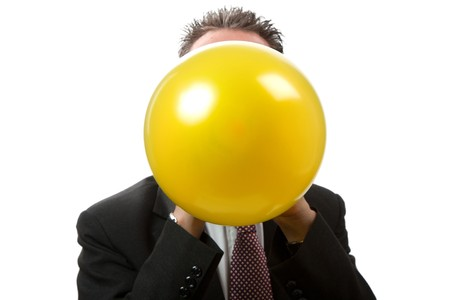 facing the camera: A mid thirties business man blowing up a yellow balloon.  Facing camera.   Studio isolated on a white background.