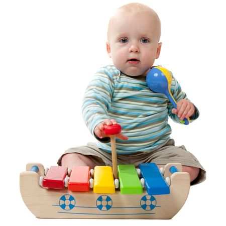 A baby boy playing with a rattle and a xylophone.  Isolated on white. photo