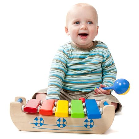 xylophone: A baby boy with a big dribble playing with a rattle and a xylophone.  Isolated on white.