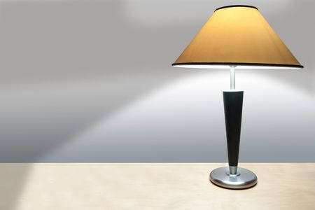 lamp shade: A simple lamp with yellow shade on a wooden desk casting a shadow onto a plain wall.