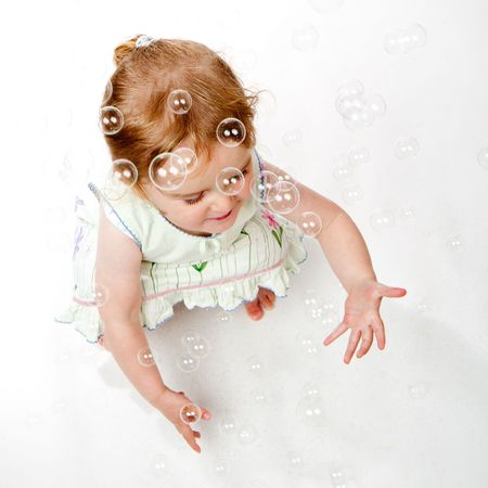 A studio shot of a two year old girl trying to catch soap bubbles. photo